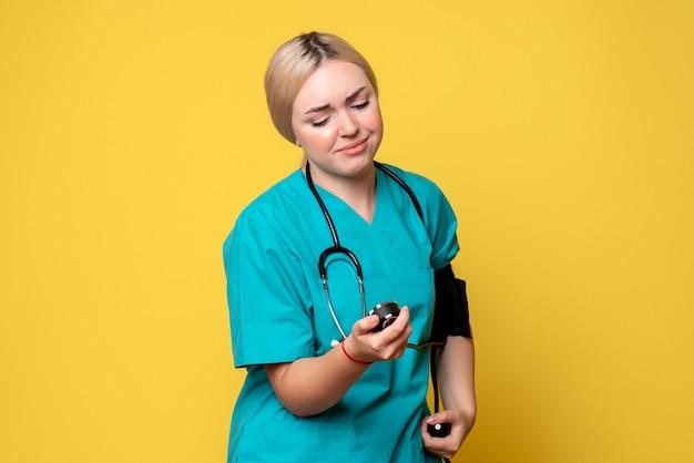 Medico femminile di vista frontale che controlla la sua pressione sull'ambulanza del virus dell'infermiera dell'ospedale covid-19 del medico sanitario della scrivania gialla
