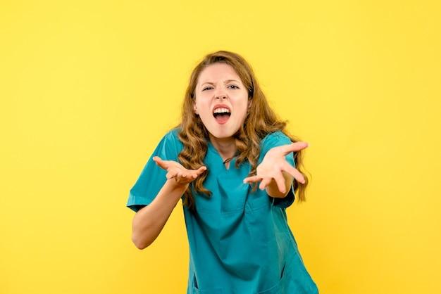 Вид спереди женщина-врач смущена на желтом пространстве