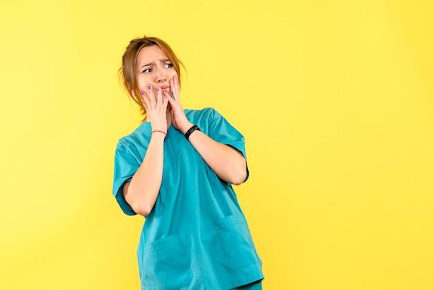 Medico femminile di vista frontale confuso sullo spazio giallo