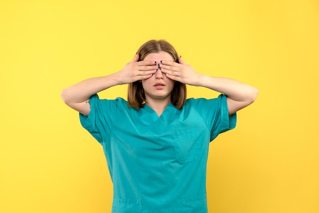 노란색 공간에 그녀의 눈을 덮고 전면보기 여성 의사