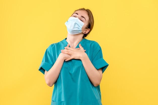 Medico femminile di vista frontale deliziato nella maschera su pandemia covid dell'ospedale di salute del fondo giallo