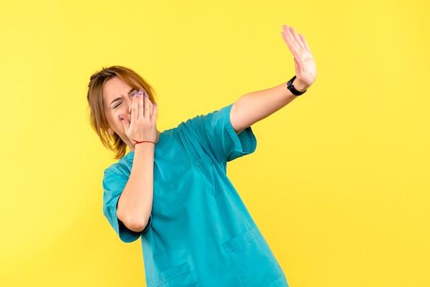 노란색 공간에 불쾌한 전면보기 여성 의사