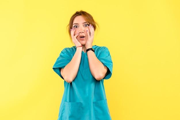 노란색 공간에 흥분된 전면보기 여성 의사