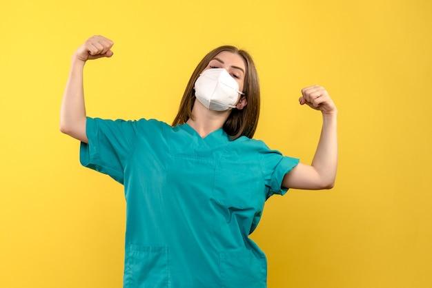노란색 공간에 flexing 전면보기 여성 의사