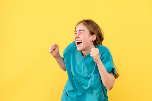 Front view female doctor happily excited on yellow background emotion hospital medic health