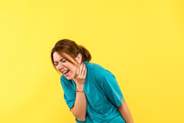 黄色の空間で呼吸の問題を抱えている正面図の女性医師