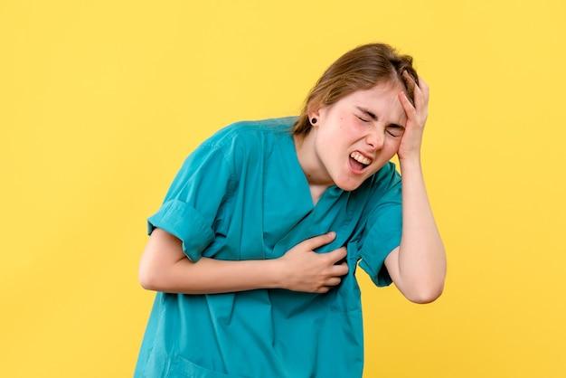 Вид спереди женщина-врач с головной болью на желтом фоне, здоровье, медик, больница, эмоция