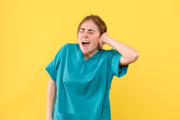 Medico femminile di vista frontale che ha dolore sull'emozione dell'ospedale del medico di salute del fondo giallo