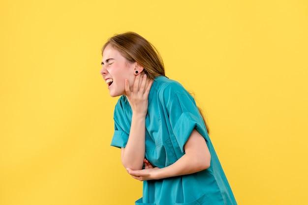 Вид спереди женщина-врач с болью в горле на желтом фоне, здоровье, медик, больница, эмоция