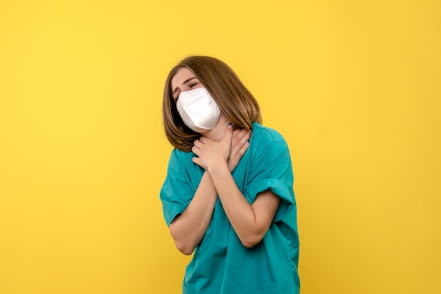 Вид спереди женщина-врач с болью в горле на желтом пространстве