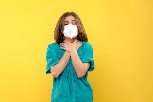 Front view female doctor having sore throat on yellow space
