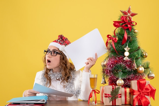 Medico femminile di vista frontale dietro la sua tabella che tiene i documenti