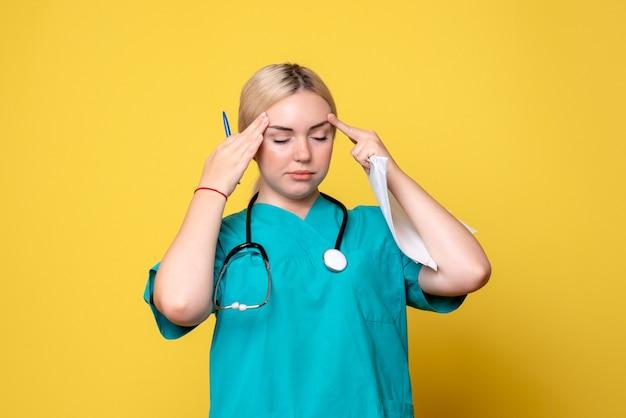 Medico femminile di vista frontale che tiene analisi e documenti che hanno mal di testa, ospedale infermieristico covid del medico di salute del coronavirus