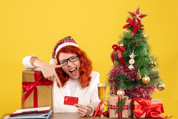 Front view female doctor holding bank card around xmas presents and tree