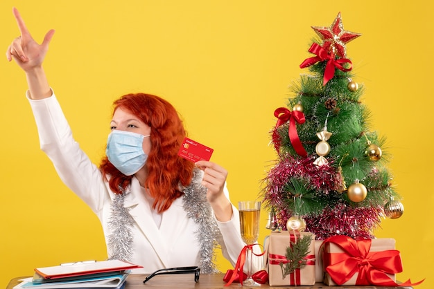 Вид спереди женщина-врач, держащая банковскую карту