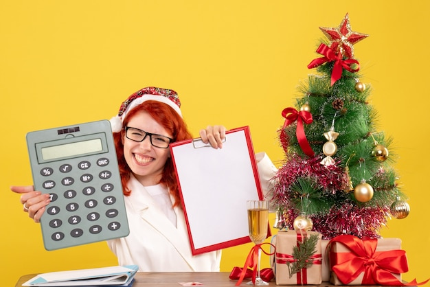크리스마스 선물 및 나무 주위에 계산기를 들고 전면보기 여성 의사