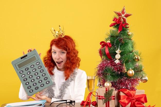 クリスマスプレゼントと木の周りに電卓を保持している正面図の女性医師