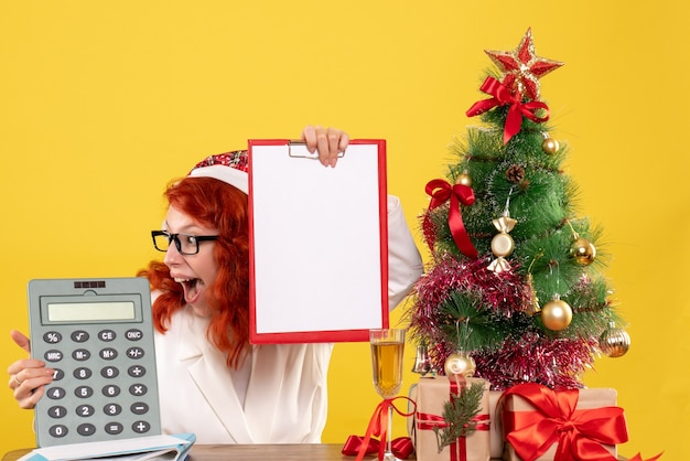Front view female doctor holding calculator around xmas presents and tree