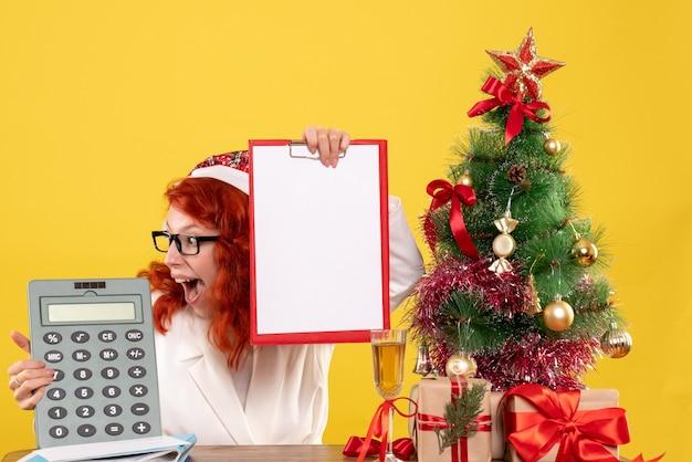 Calcolatore femminile della tenuta del medico di vista frontale intorno ai regali e all'albero di natale