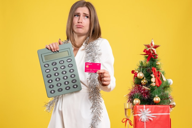 Front view female doctor holding calculator and bank card