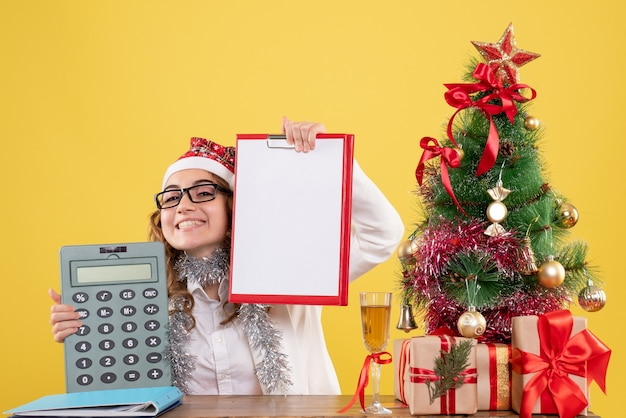 Front view female doctor holding calculator and file note