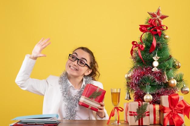Вид спереди женщина-врач, держащая рождественский подарок