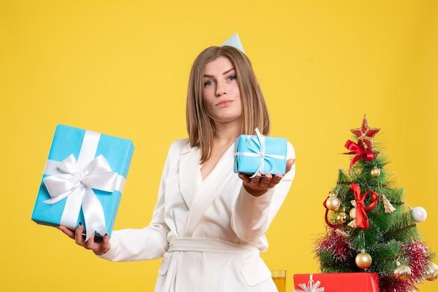 Medico femminile di vista frontale che tiene i regali di natale
