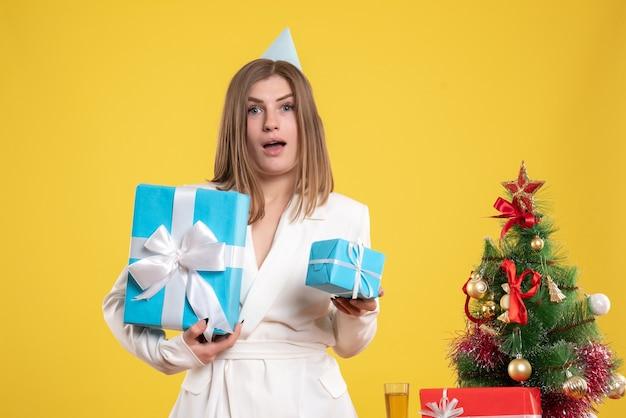 クリスマスプレゼントを保持している正面図の女性医師