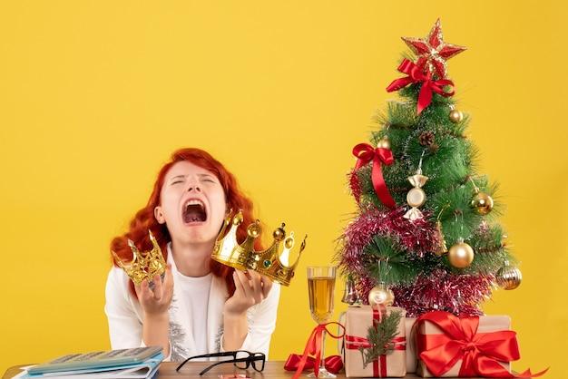 크리스마스 트리와 선물 주위에 크라운을 들고 전면보기 여성 의사