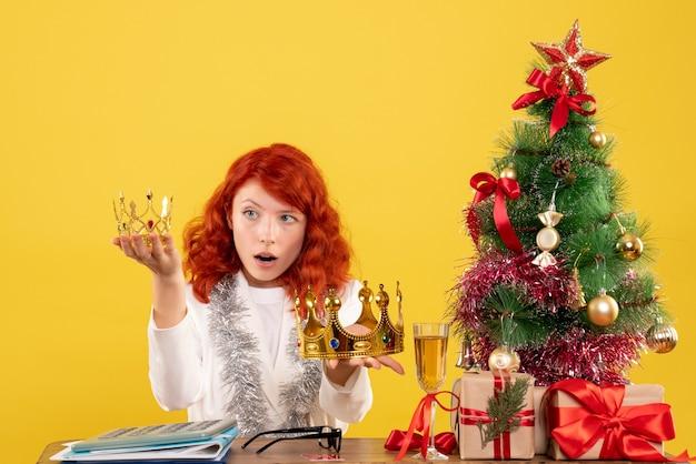 Medico femminile di vista frontale che tiene le corone intorno all'albero di natale e ai regali