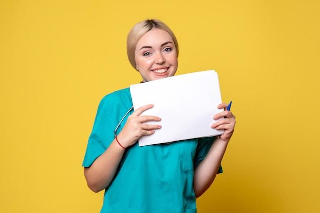 Medico femminile di vista frontale che tiene i documenti differenti, ospedale covid-19 dell'infermiera del medico di salute di pandemia del virus