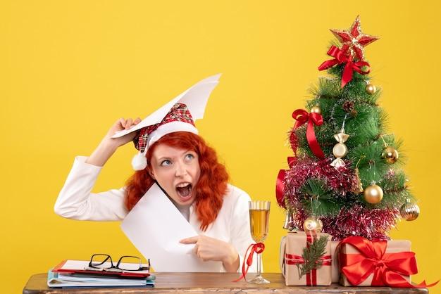문서를 들고 크리스마스 선물에 앉아 전면보기 여성 의사