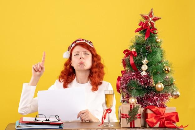 Вид спереди женщина-врач, держащая документы за столом с грустными подарками