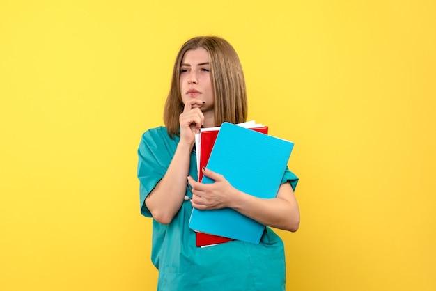 Вид спереди женщина-врач, держащая документы на желтом пространстве