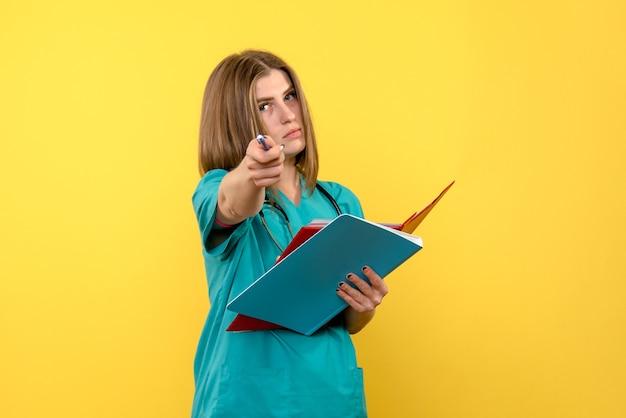 黄色い床の病院の救急措置に関する文書を保持している正面図の女性医師