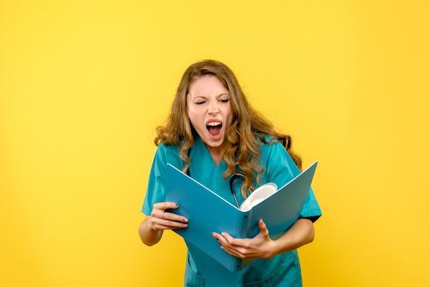 노란색 공간에 문서를 들고 전면보기 여성 의사
