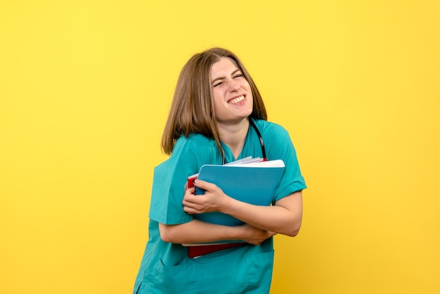 黄色のスペースにドキュメントを保持している正面図の女性医師
