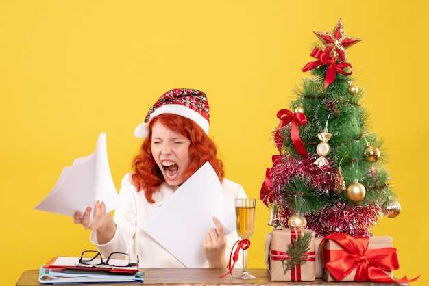 Front view female doctor holding documents and sitting with christmas presents