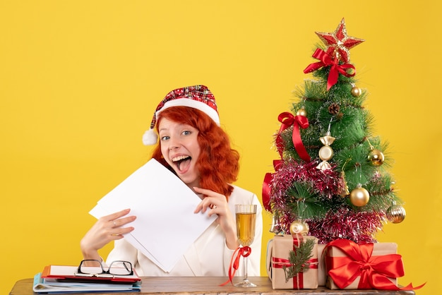 Front view female doctor holding documents behind table with presents