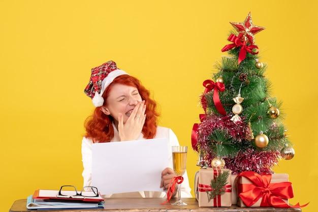Medico femminile di vista frontale che tiene i documenti dietro il tavolo con i regali