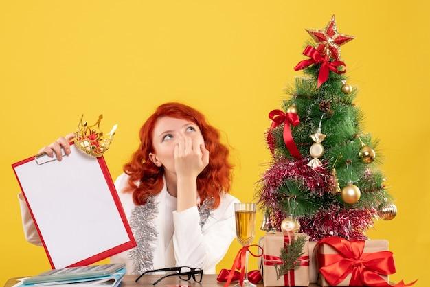 크리스마스 트리와 선물 주위에 파일 메모를 들고 전면보기 여성 의사