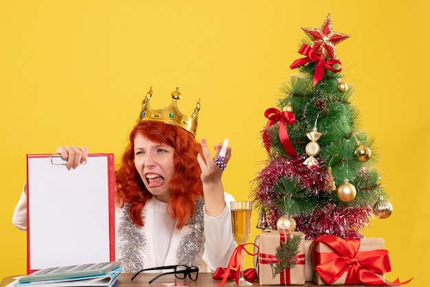 Front view female doctor holding file note around xmas tree and presents