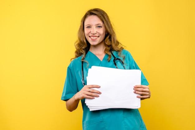 Medico femminile di vista frontale che tiene i file sullo spazio giallo chiaro
