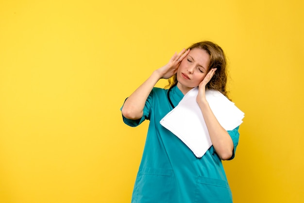 Front view female doctor holding files on the yellow space