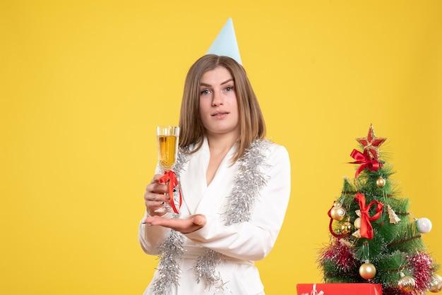 Medico femminile di vista frontale che tiene vetro di champagne e che celebra