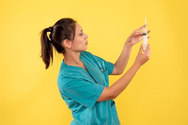 노란색 바탕에 주사를 들고 전면보기 여성 의사