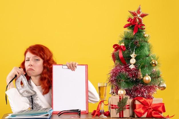 Вид спереди женщина-врач, держащая маску вокруг рождественской елки и подарков