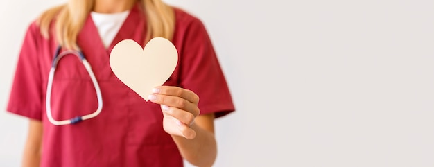 Front view of female doctor holding paper heart with copy space