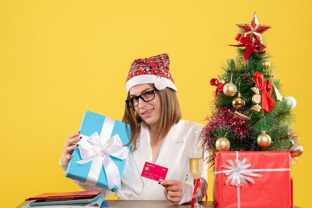 プレゼントと銀行カードを保持している正面図の女性医師