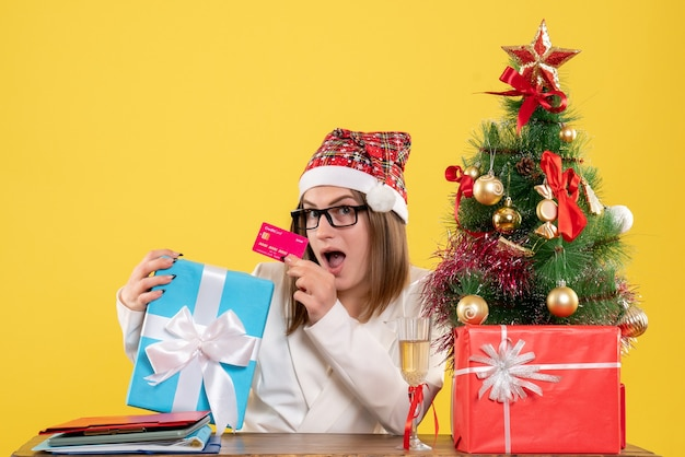 Вид спереди женщина-врач, держащая подарок и банковскую карту